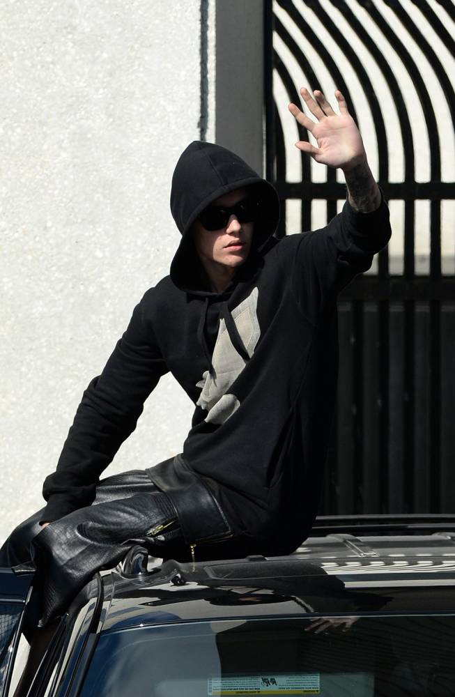 January 23, 2014: Justin Bieber is released from jail wearing a new hoodie, leather pants, red hi-top trainers, and a big smile as he waves to press and fans from the top of one of his waiting SUV's. Mandatory Credit: INFphoto.com Ref: infusmi-11/13|sp|
